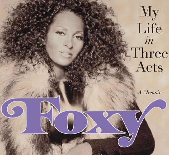 Pam Grier posing for the camera wearing the fluffy jacket for the cover picture of her memoir,  Foxy: My Life in Three Acts.