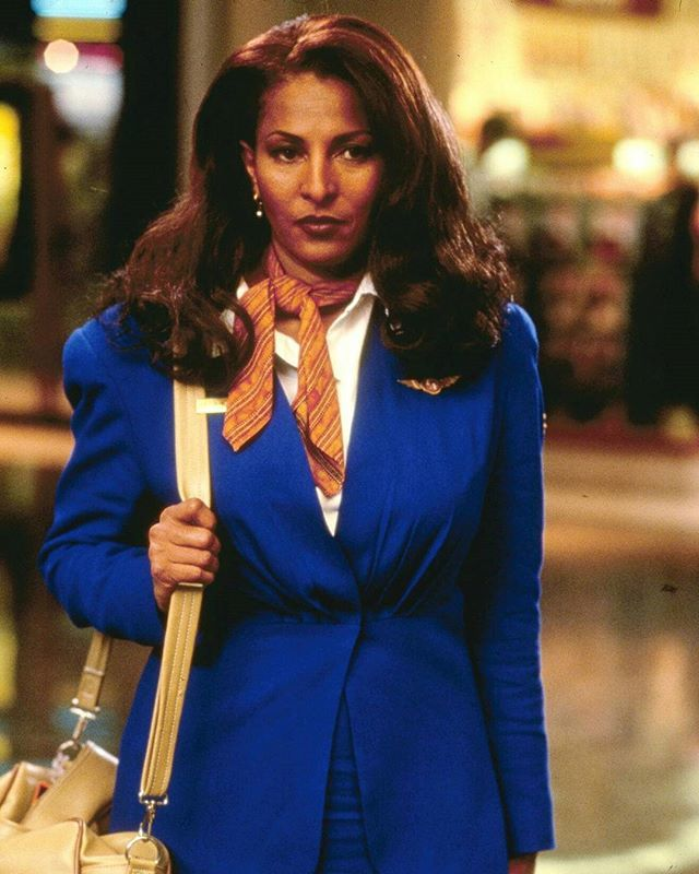 Jackie Brown is wearing a blue suit. She is looking away from the camera with not so impressed face. She is the title role in the movie Jackie Brown.