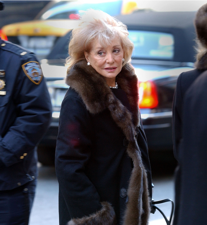 Barbara Walters turning back wearing a long black coat