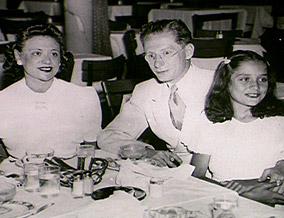 Journalist Barbara Walters with her father and mother siting on the table.