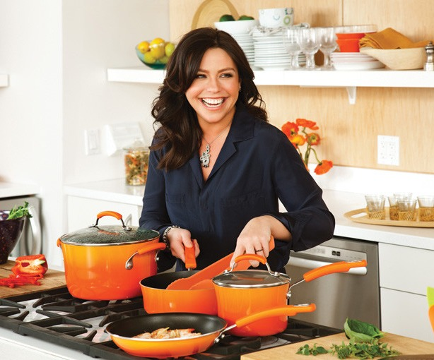 Rachael Ray cooking in the kitchen,. She is looking right with a big smile on her face. She hosts several Food Network shows.