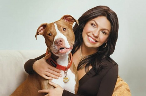 Rachael Ray smiling with grace. She is holding her dog, Pit bull. She is TV shows host.