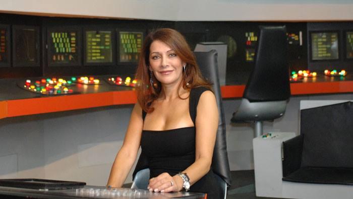 Marina Sirtis sitting in a chair wearing a black dress