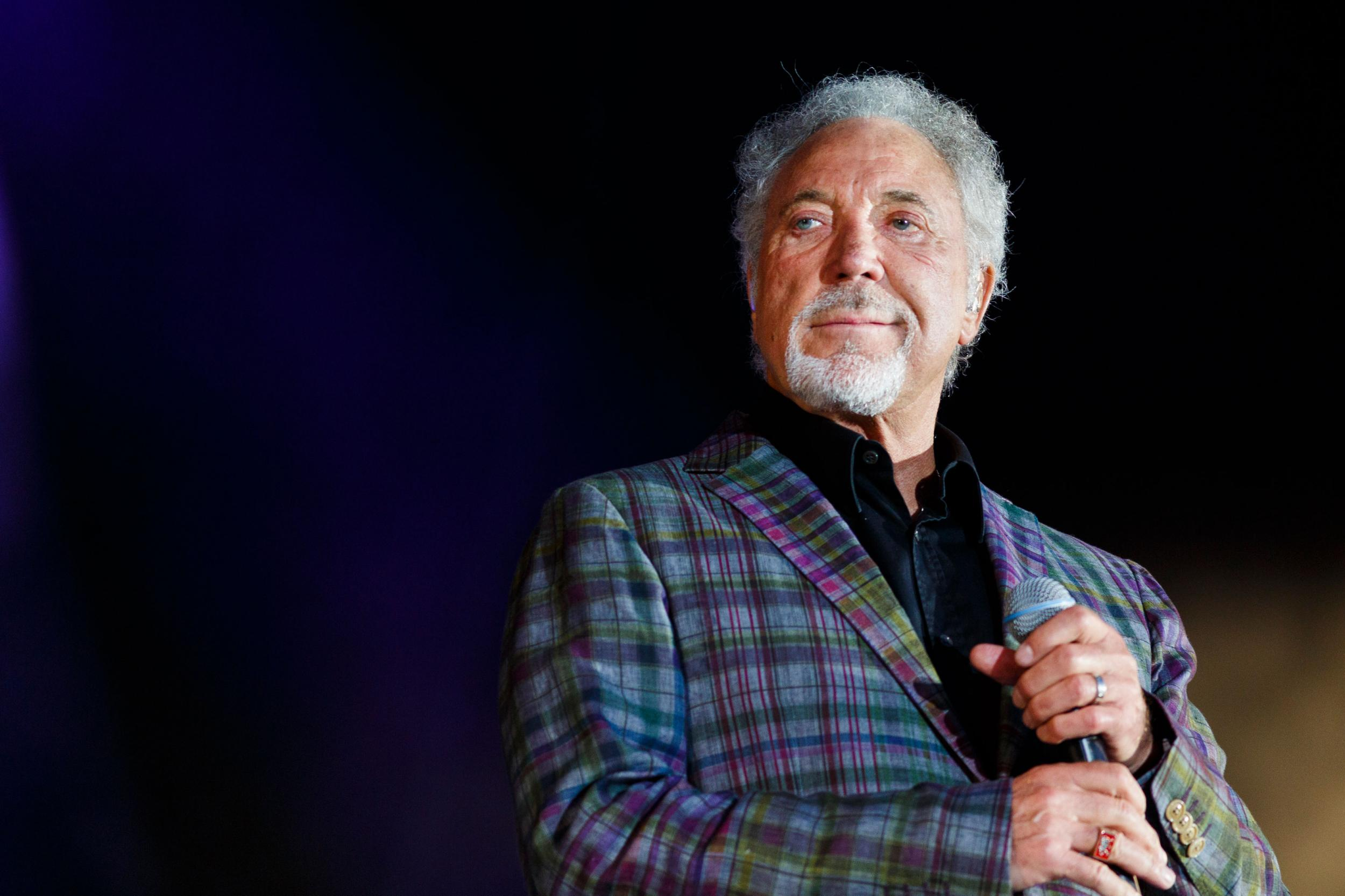 Tom Jones in a stage wearing a coat. He is gripping a mic in his hand