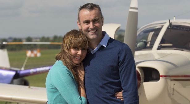Carol Vorderman and Graham Duff hugs as they take a picture at a air field.