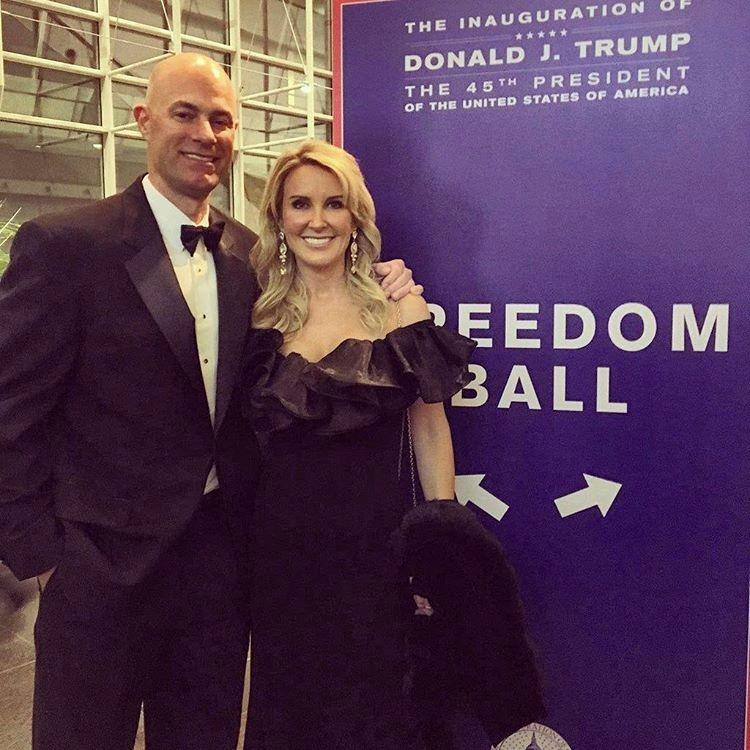 Heather Childers wearing an off-shoulder black dress standing beside Thomas in a tuxedo