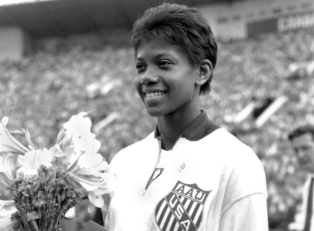 Wilma Rudolph holds a bouquet of flower after the competition.