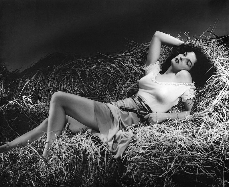 Jane Russell's erotic looks while she rests on straw. The picture was used for the promotion of movie The Outlaw (1943).