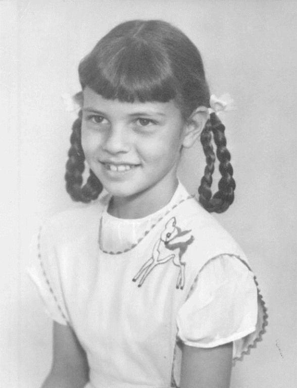 A childhood photo of Raquel. She is wearing a white dress and has two ponytail braids