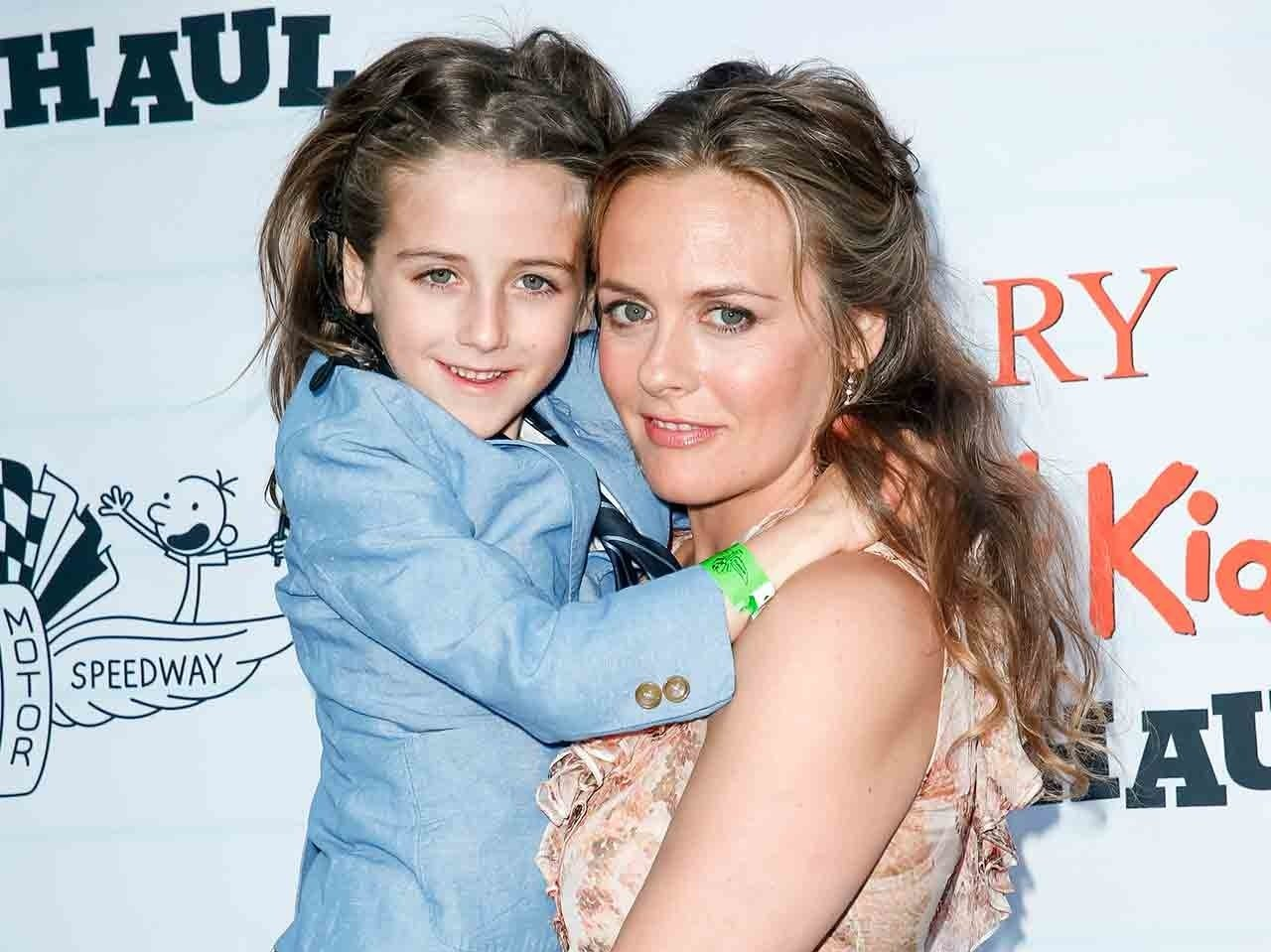 Alicia Silverstone carrying her son, they both are looking at the camera.
