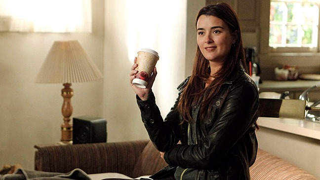 Cote de Pablo is carrying a coffee cup in her hand and is smiling.