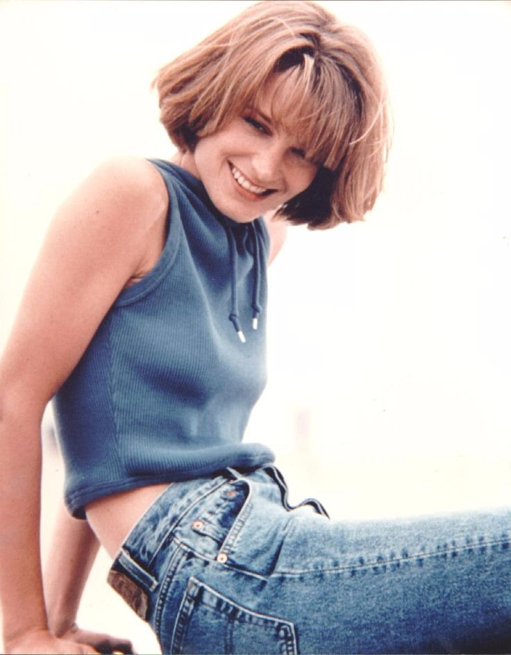 Young Bridget Fonda is smiling and looking away from the camera. She is wearing denim pants and sleeveless croptop.