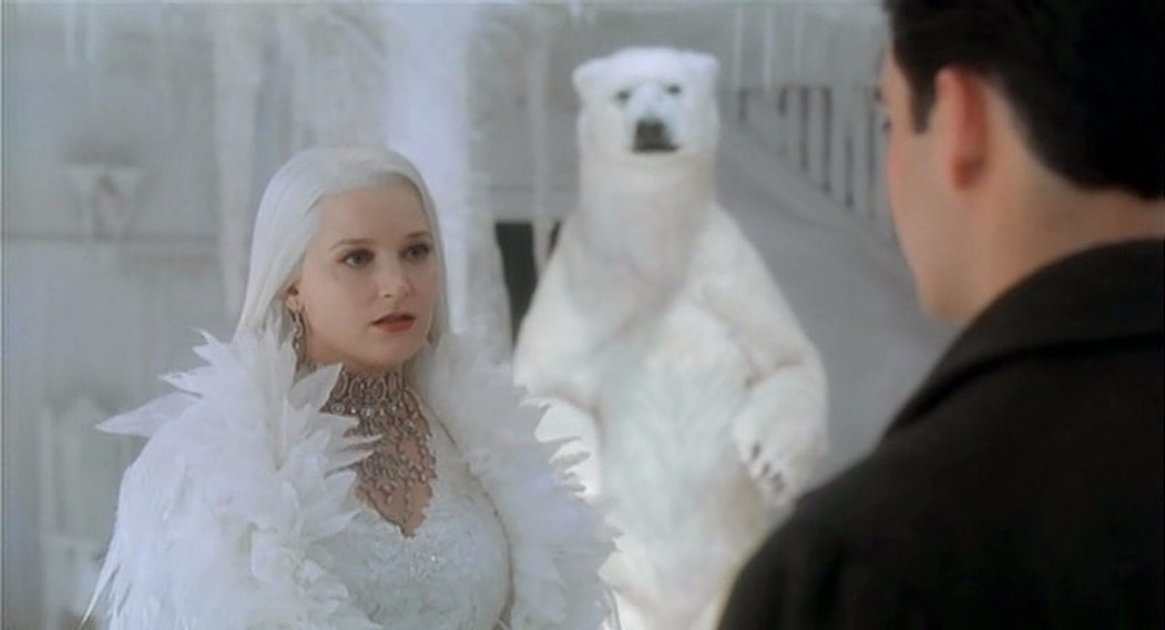 Bridget Fonda in the role of Snow Queen, which she played in the TV movie, Snow Queen. In the background, there is a polar bear.