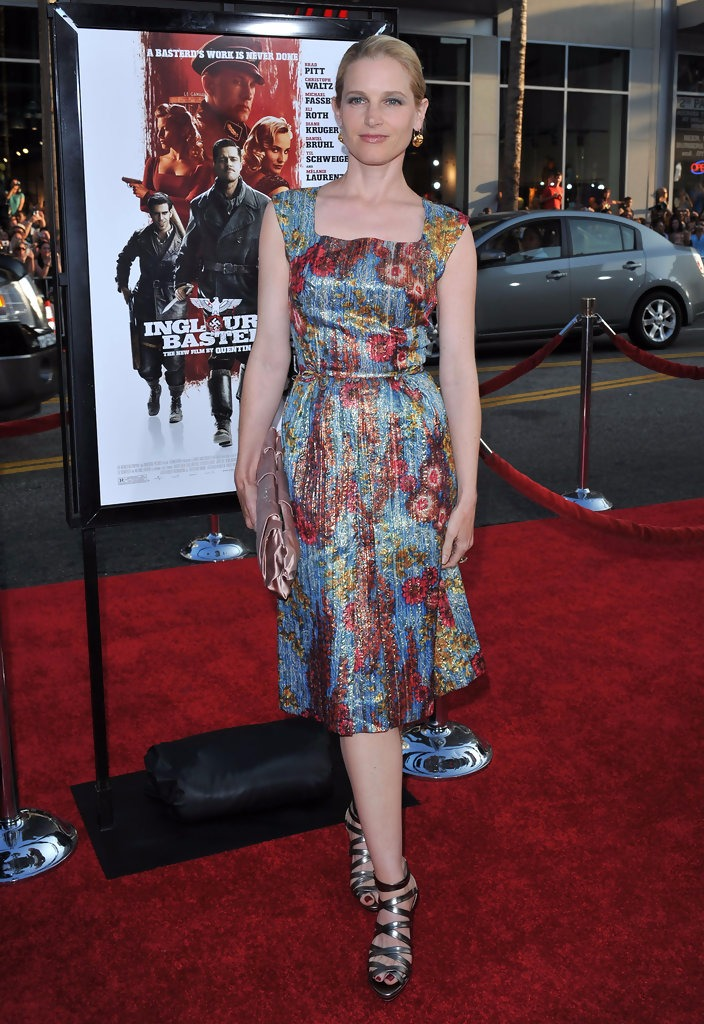 Bridget Fonda is seen wearing a floral patterned dress paired with silver heels. She is holding a clutch.