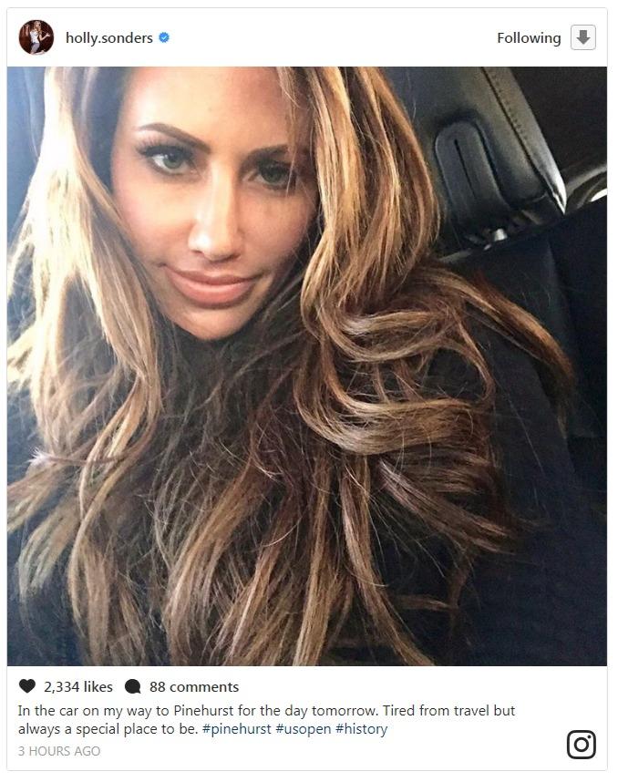 Holly Sonders is inside a car, taking a selfie.