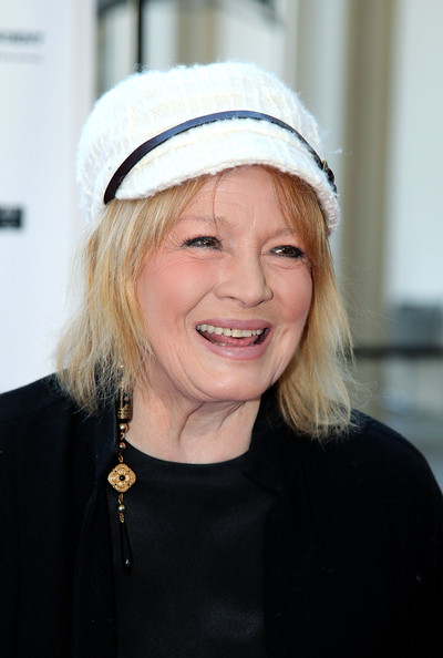 Angie smiling. She is wearing a white hat and black attire
