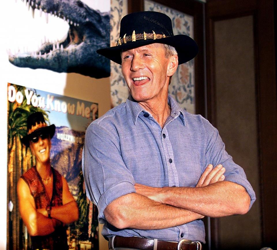 Paul Hogan standing with his arms folded wearing a hat while there's his poster in the background