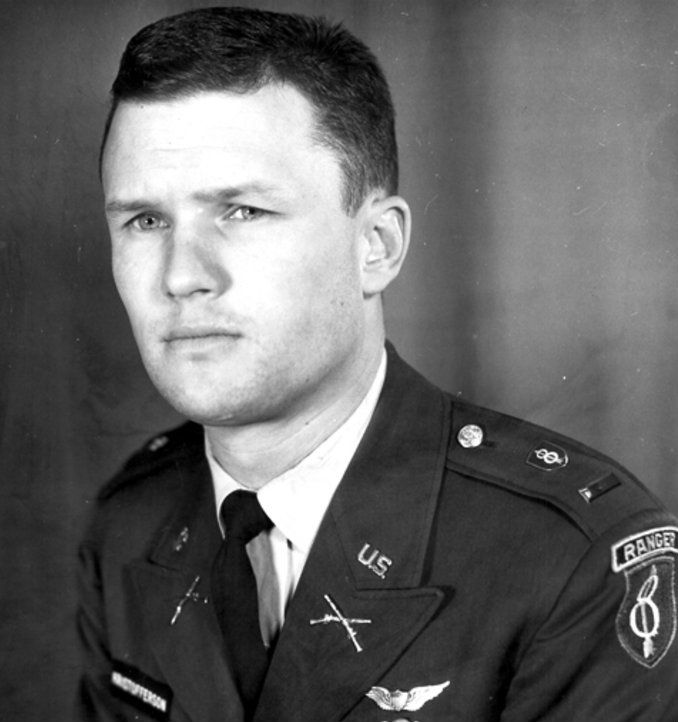 A black and white potrait of Kris in army uniform. The Ranger School badge is prominently displayed
