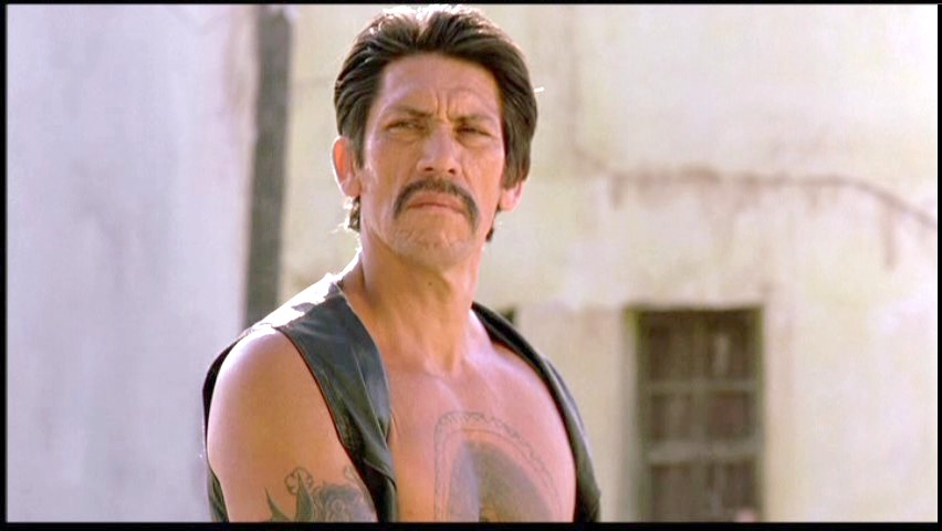 Danny Trejo is wearing a half leather dress and has a short hair
