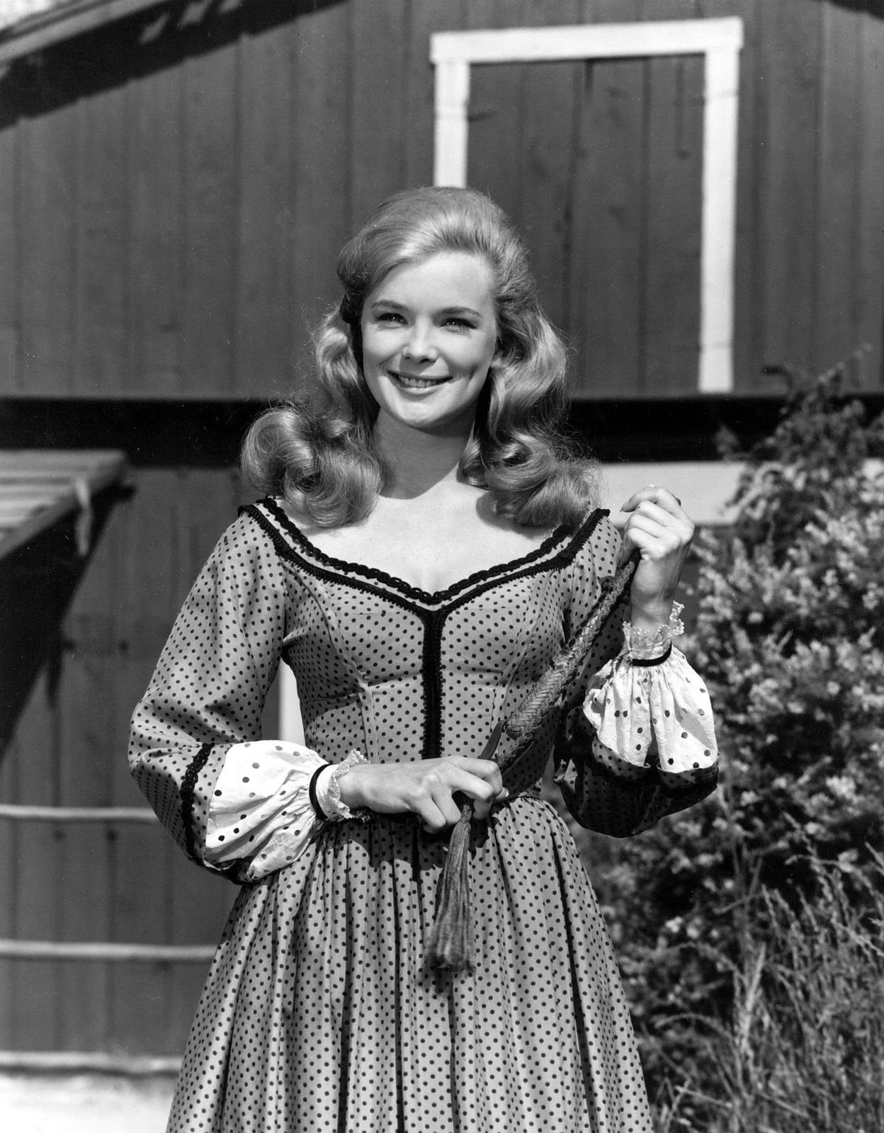black and white picture of Linda Evans holding a whip