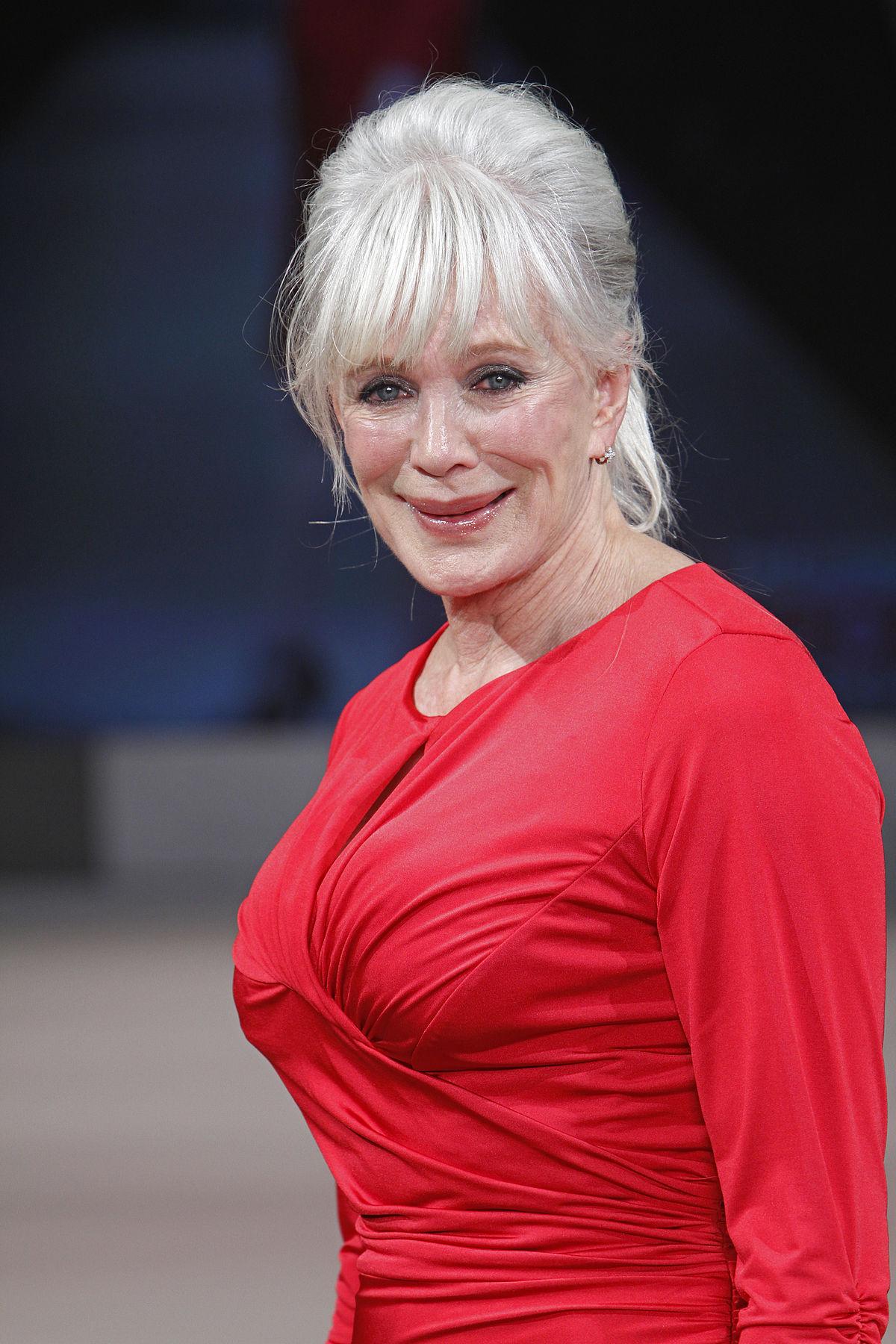Linda Evans smiling wearing a red dress