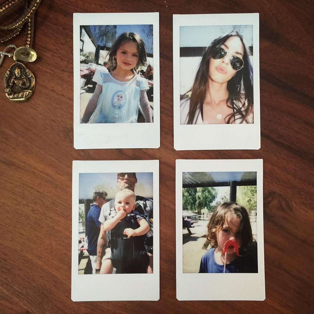 Pictures of Megan Fox and her three sons are on a table.