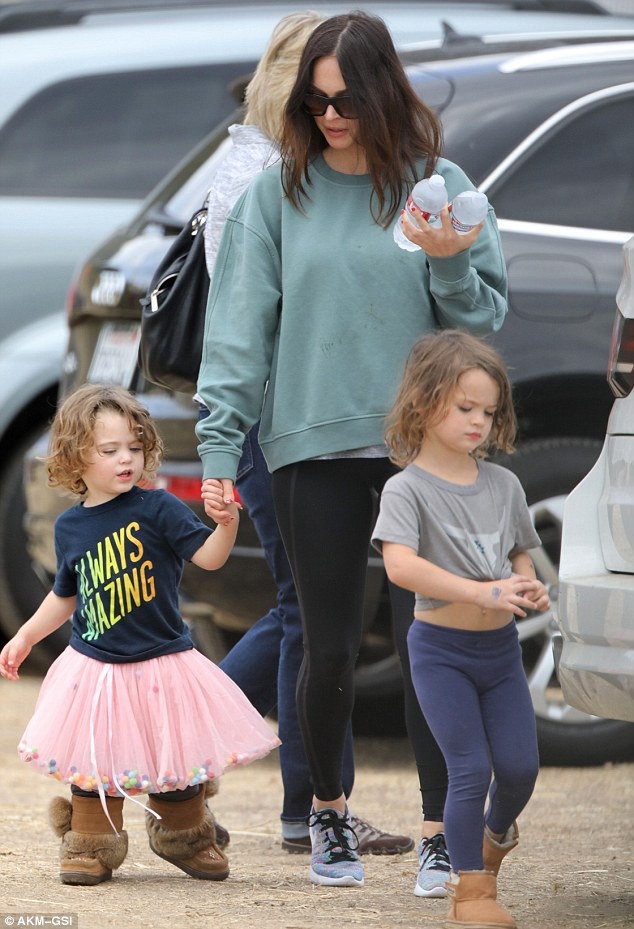 Megan Fox is holding hand of her son Bodhi Ransom in one hand and two bottles of water in the other. Her elder son Noah Shannon is walking in front of them.