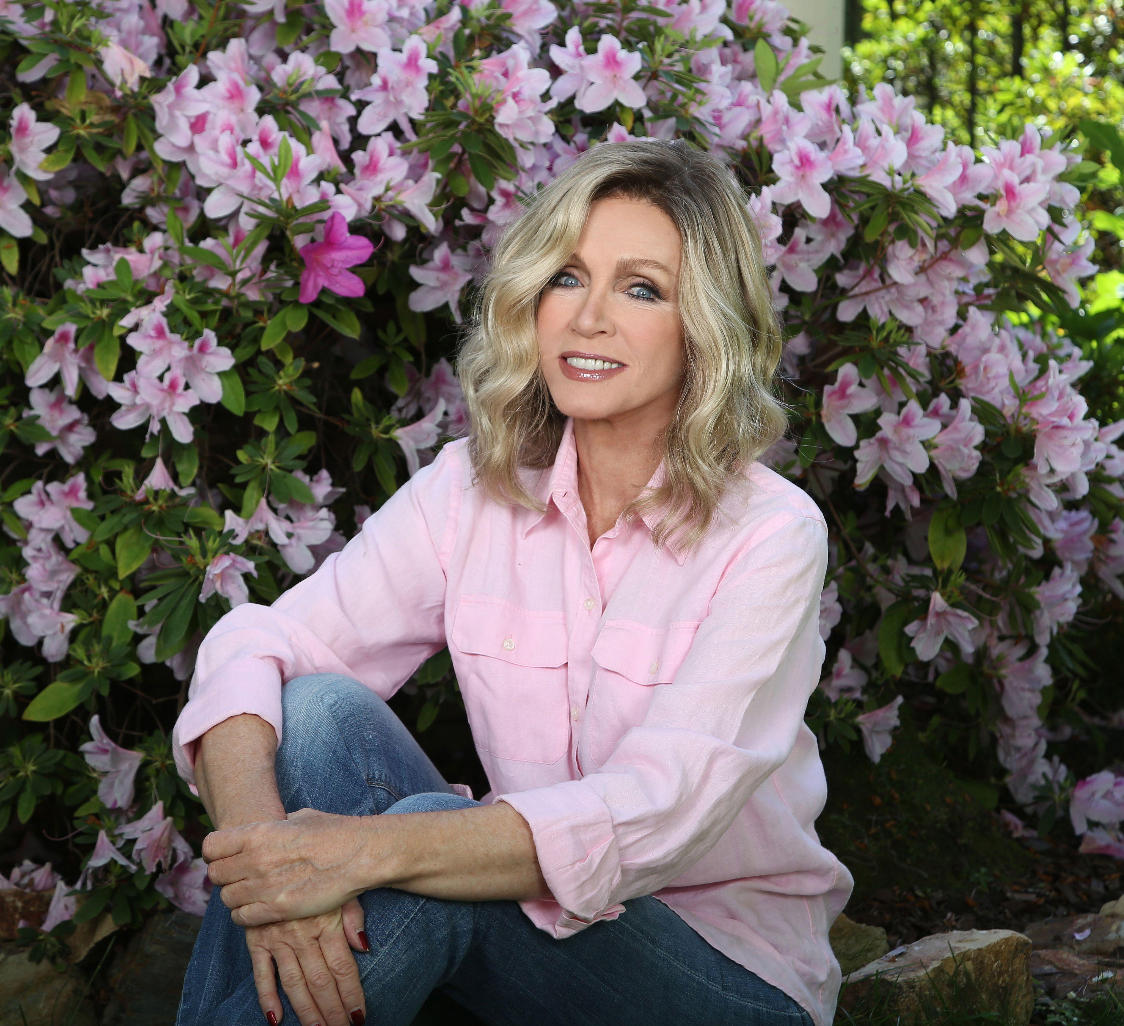 Donna Mills putting her hands around her knee with flowers on her background