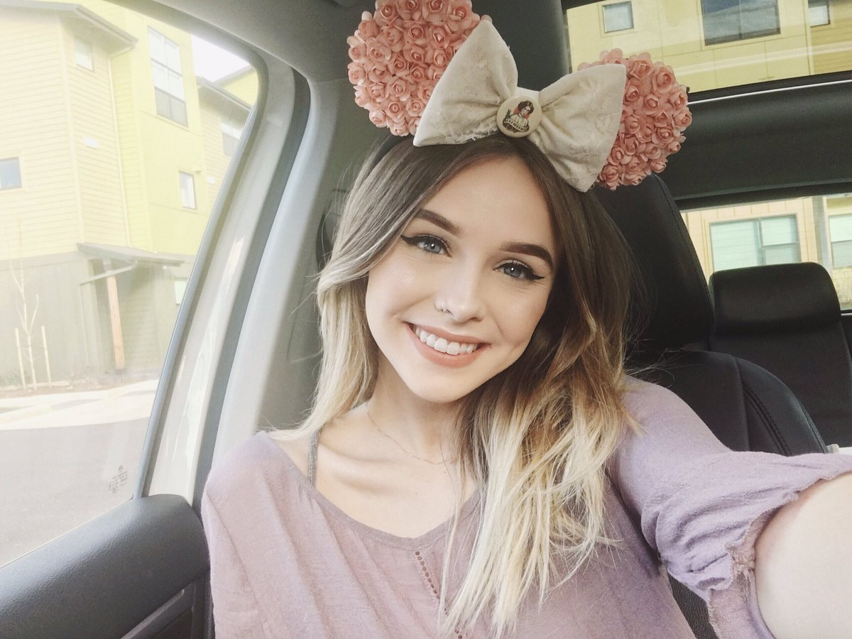 Acacia Brinley is taking a selfie wearing a bow on her head