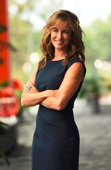 Suzy Kolber is wearinfg a simple dark blue dress and smiling for the camera with her hands folded.