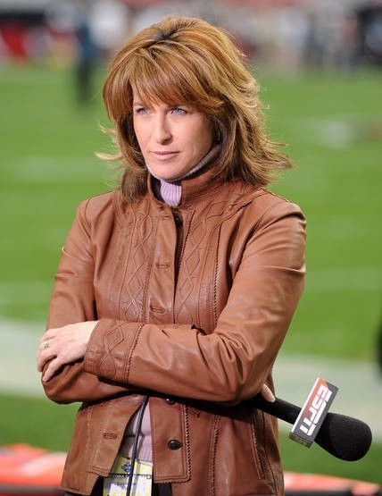Suzy Kolber looks like she is concentrating on the game is reporting, she has an ESPN mic on her hand.
