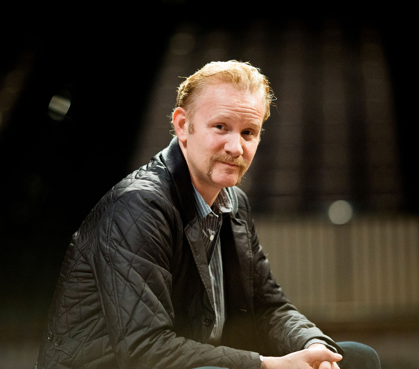 Morgan Spurlock looks dashing in his black jacket and lined shirt. He is sitting and giving intense looks facing the camera