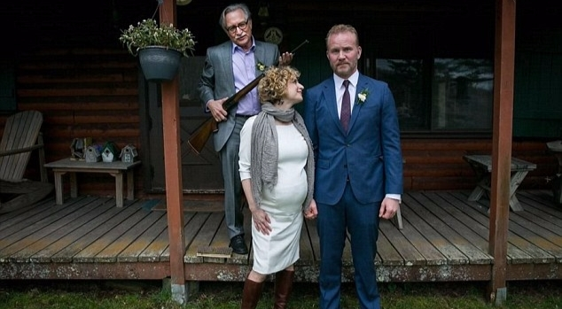 Morgan Spurlock and his pregnant bride posing with a man who's holding a shotgun.  Morgan is facing a camera while his wife is looking at him with smile.