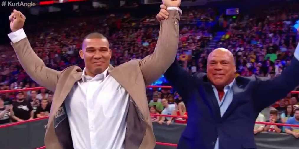 Kurt Angle holding his son Jason Jordan's hand and raising it high. Both men are in a suit.