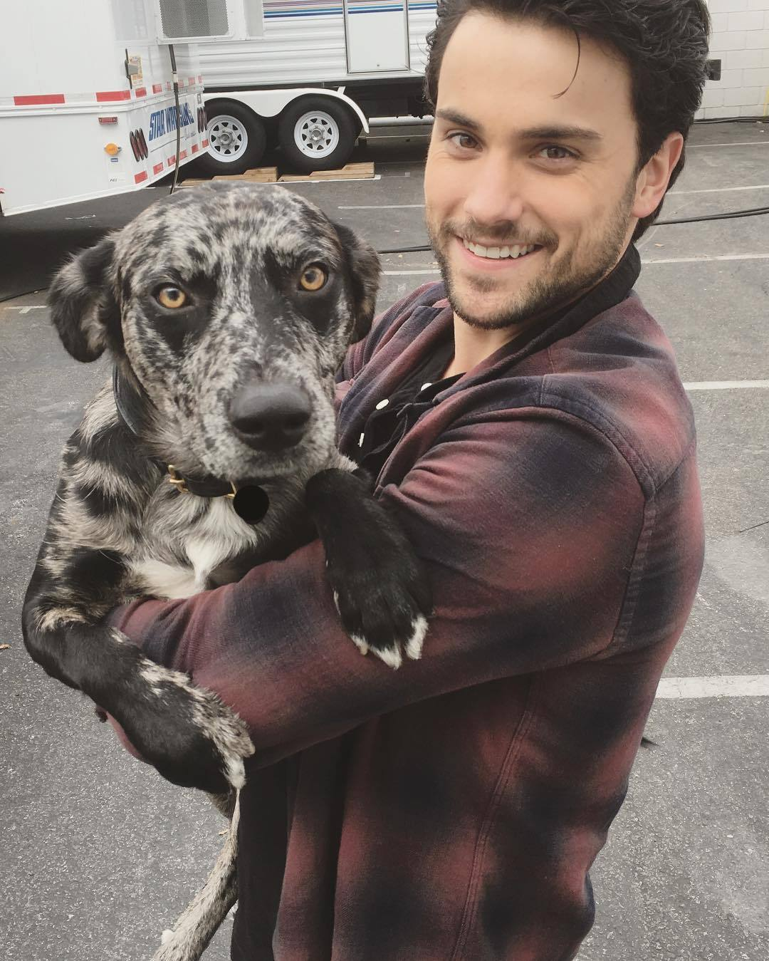 Jack Falahee posing with his dog for a photo