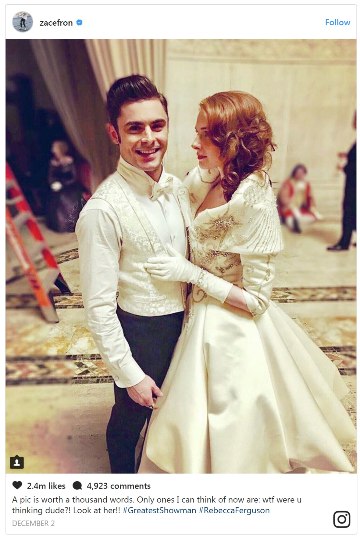 Zac Efron and Rebecca Ferguson are dressed up in a matching white dress. They are standing close and Rebecca is looking into Zac's eyes.