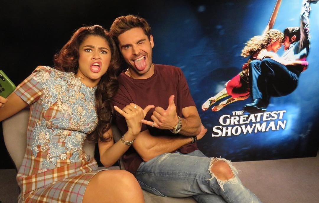 Zac Efron and Zendaya sitting cozy during The Greatest Showman promotion. The pair are giving a rock sign from their hands gesture.