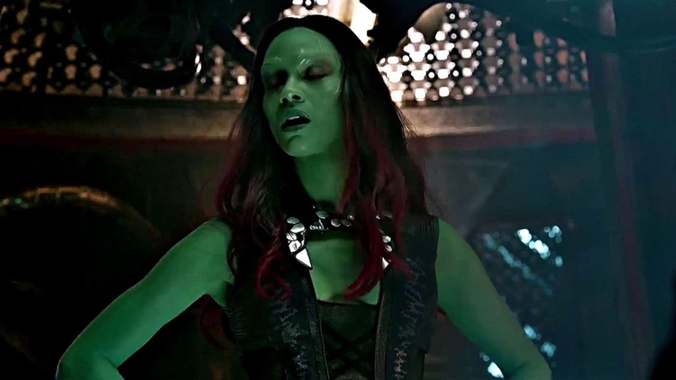 Zoe Saldana as Gamora is standing and has worn a large choker on her neck