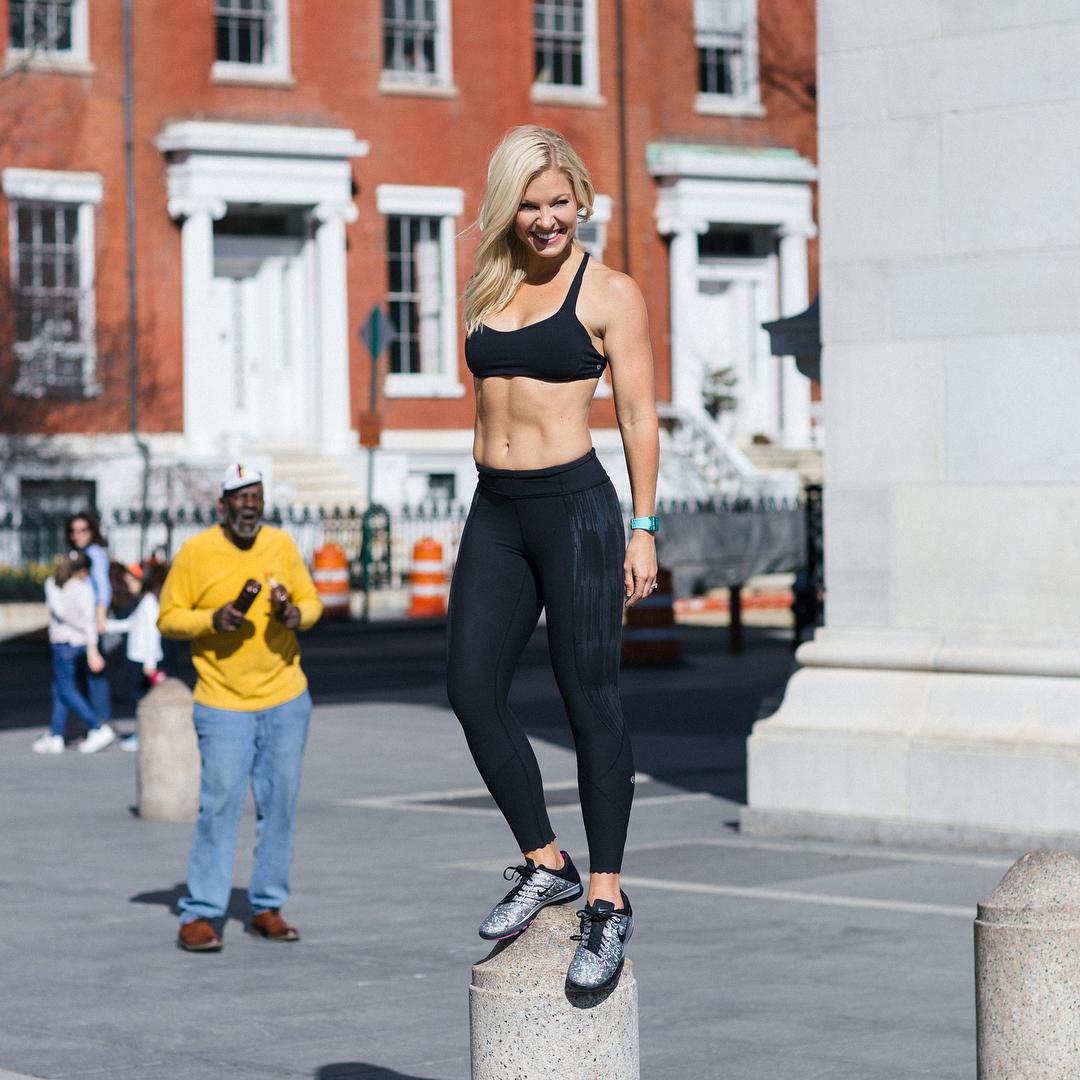 Anna Kooiman standing on a concrete cylinder in sexy gym wear