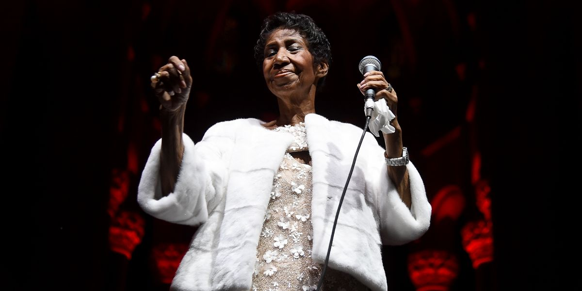 Aretha Franklin is wearing white furry coat while holding a mic in her left hand