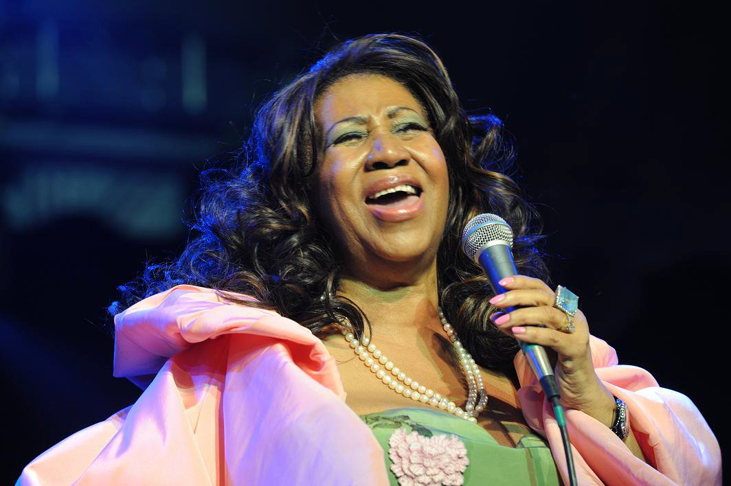 Aretha Franklin is holding a mic in her hand