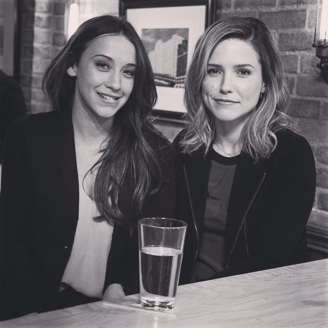 Stella Maeve and Sophia Bush from Chicago P.D sitting next to each other, there's a half empty glass on the table