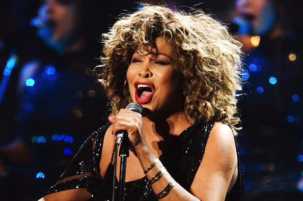 Tina Turner singing in one of her events. She is holding the mic while she sings. She is wearing a glittery black sleeveless dress.