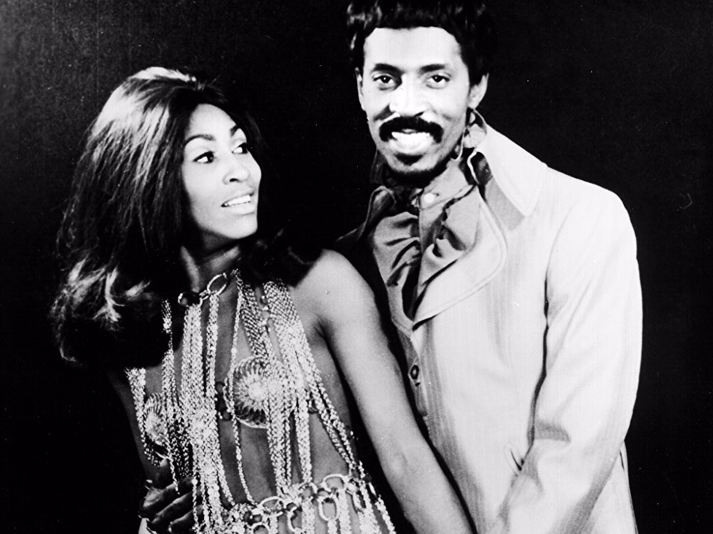 Tina and Ike Turner posing as a couple when they were happily married. Tina is wearing a dress made from metal jewels and is looking at Ike romantically while Ike is looking at the camera and smiling.