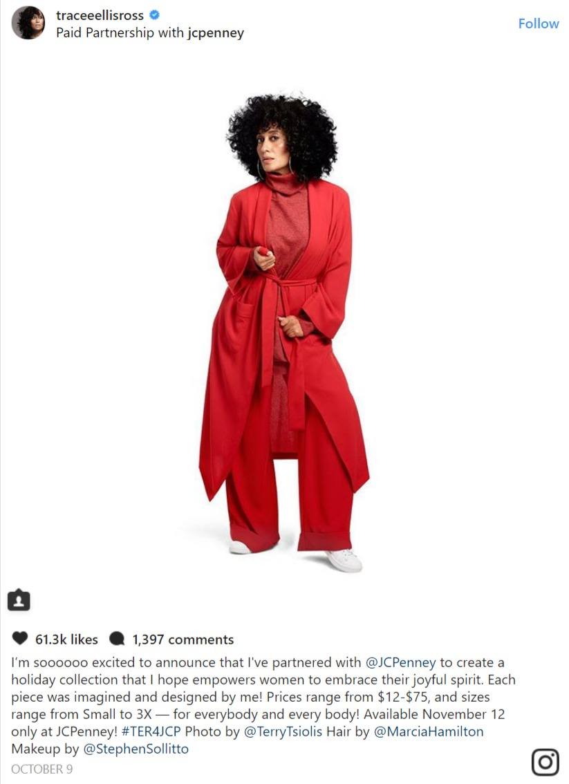 Tracee Ellis Ross tugging at the ends of her belt of her jumpsuit overall