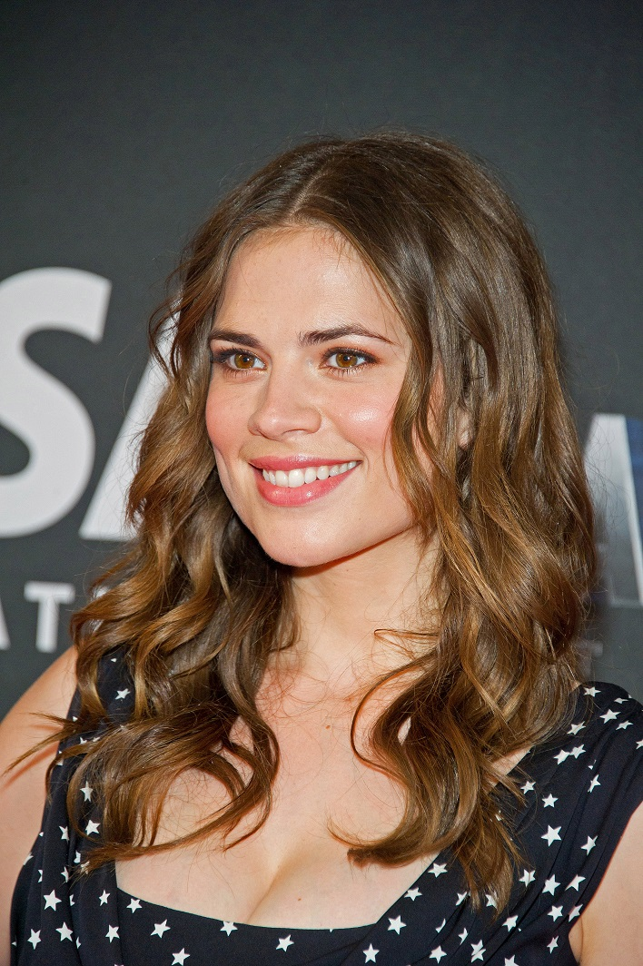 Hayley Atwell seen wearing a black top with white stars spread all over the cloth. She is smiling in the picture.