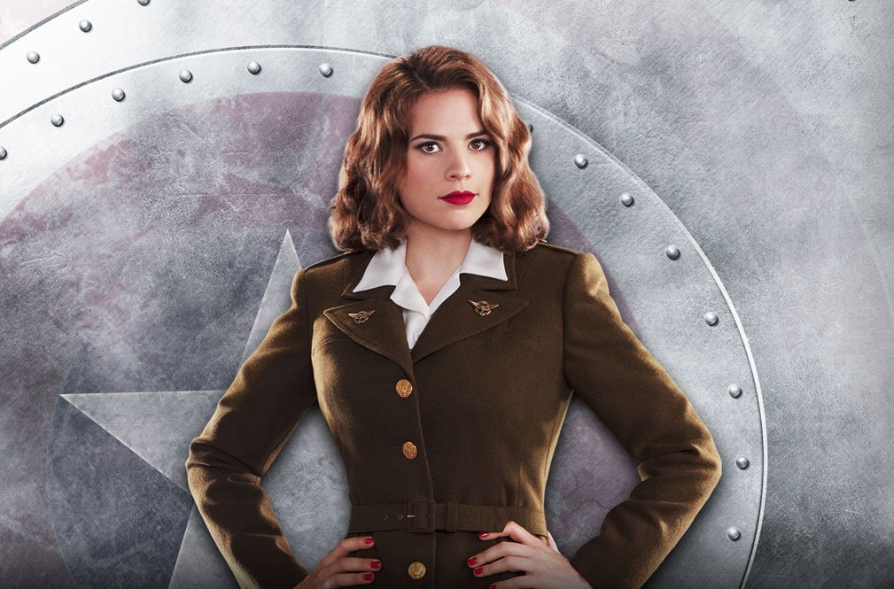 Hayley Atwell posing as Agent carter. She is wearing a military style uniform and has her hands on her hips