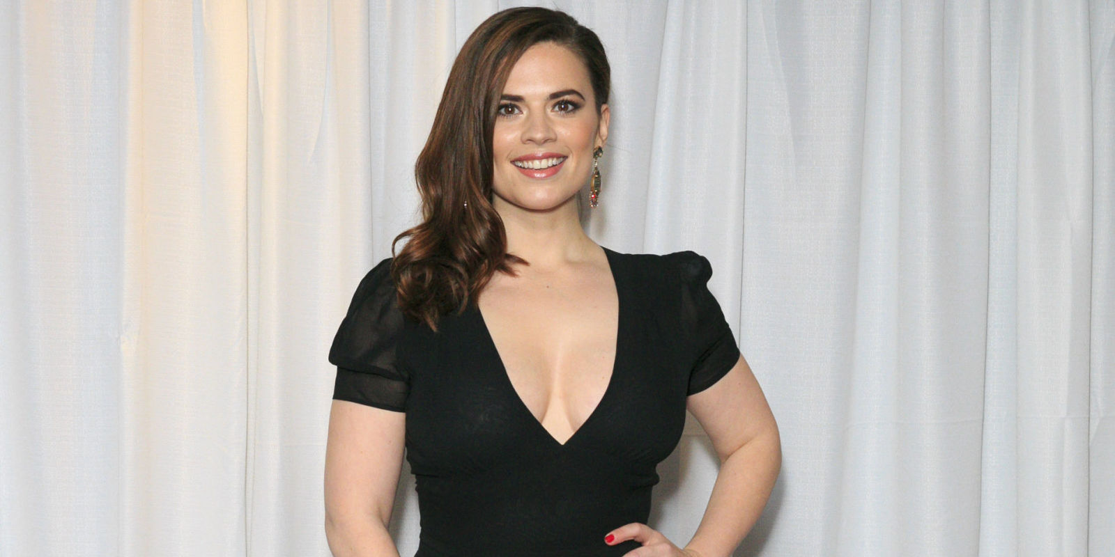 Hayley Atwell posing in a black dress with her hands on her shoulders