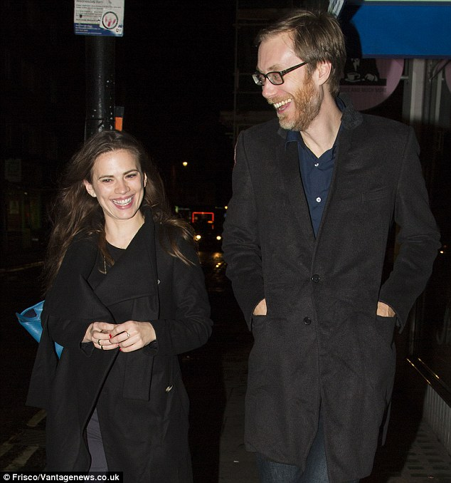 Hayley Atwell and Stephen Merchant walk together as they laugh. Merchant has his hands inside his pocket while Hayley has them together infront of her.