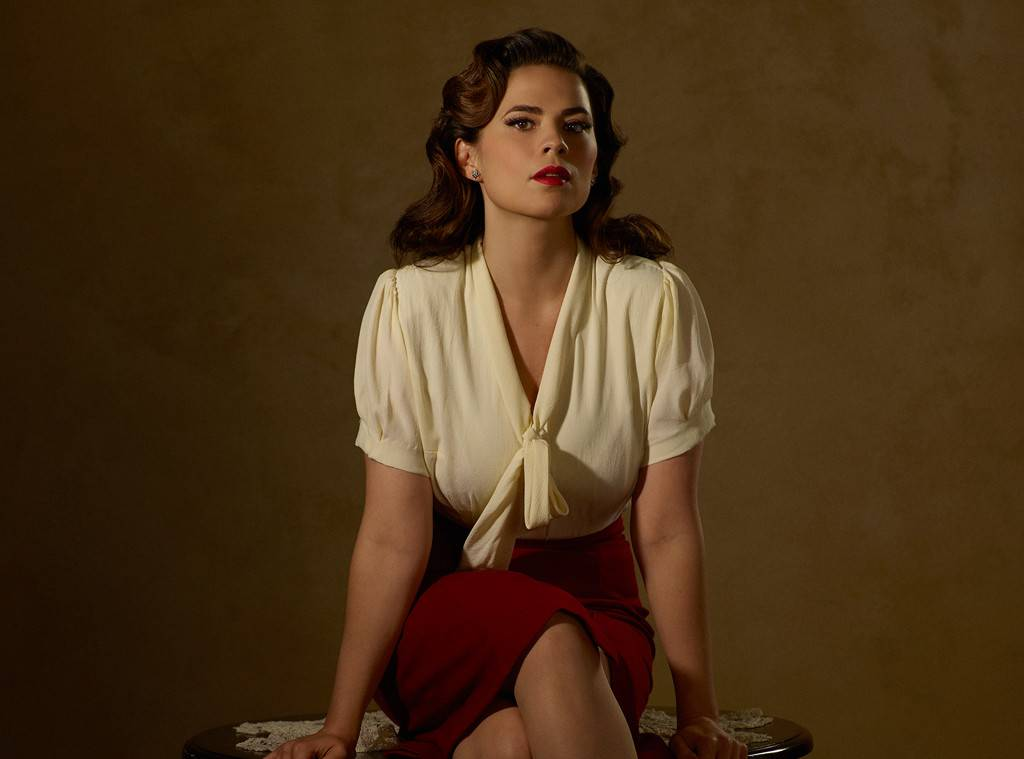 Hayley Atwell sitting on a table. She is wearing white top and red skirt